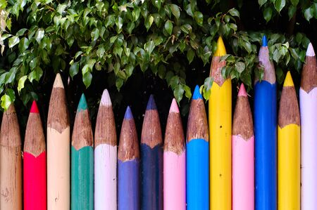 Unusual bright colour fence made of tall big pencils in row, red, blue, yellow, white, green colors, multi colored wall and green tree foliage outdoors, no people