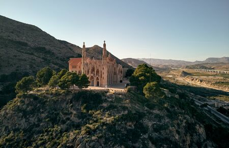 Aerial drone point of view Sanctuary of Santa Maria Magdalena rises among top of rocky mountain in Novelda town, spanish Art Nouveau masterpiece in Spain, Province of Alicante