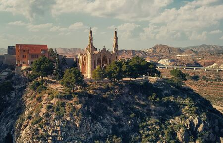 Picturesque aerial drone point of view photography of Sanctuary of Santa Maria Magdalena rises on top of rocky mountain in Novelda town, spanish Art Nouveau masterpiece in Spain, Province of Alicante