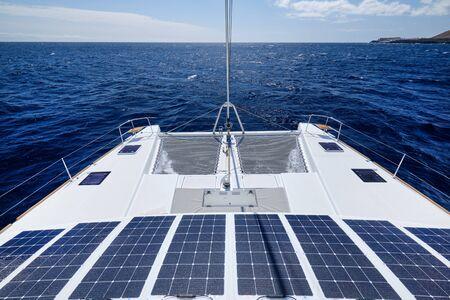Catamarano di lusso a energia solare, completamente sostenibile e alimentato da energia solare, carica le batterie a bordo di una barca a vela, nave in acque oceaniche, nessuno. Pannelli fotovoltaici concetto di energia ecologica rinnovabile