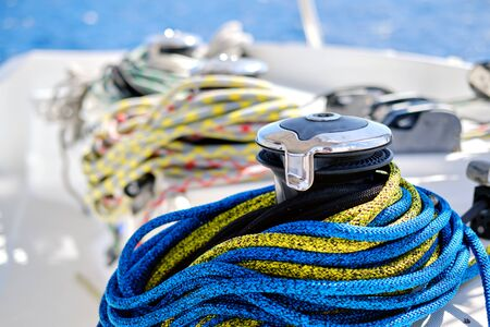 Winch with colourful yellow-blue rope on sailing boat,close up view, no people