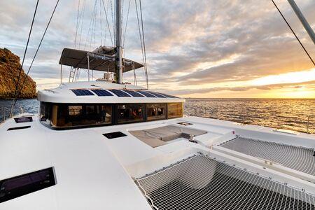 Solarbetriebener Katamaran bei Sonnenuntergang, vollständig nachhaltig und mit Solarenergie betrieben, Laden von Batterien an Bord eines Segelboots, Schiff in Ozeangewässern, niemand. Photovoltaik-Paneele erneuerbares Öko-Energiekonzept