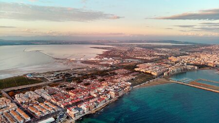 Aerial distant top eye bird view Salt Lake heap of salt and calm turquoise Mediterranean Sea, Torrevieja cityscape between of waters landscape during sunset. Province of Alicante, Costa Blanca, Spain