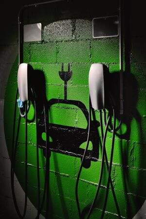 Electric vehicle charging station, free parking place green colored painted on wall symbol close up, no people Stockfoto