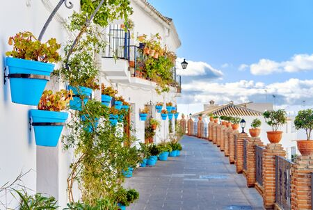 Idyllic scenery empty picturesque street of small white-washed village of Mijas. Path way decorated with hanging plants in bright blue flowerpots, Costa del Sol, Andalusia, Province of Málaga, Spain