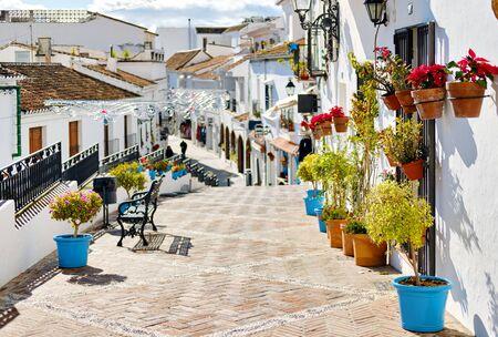 Idyllische Szene malerische Straße kleines weiß getünchtes Dorf Mijas. Weg dekoriert mit hängenden Häuserwänden Pflanzen in hellen Blumentöpfen, berühmter Ort Costa del Sol, Andalusien, Málaga, Spanien