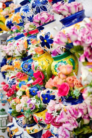 Vertical full frame image close up view background hanging on wall decorative handmade flowerpots with artificial flowers, Mijas village traditional souvenir gift, Costa Del Sol, Andalusia, Spain