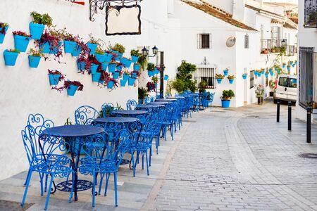 Mijas Pueblo Blanco, encantador pueblo pequeño, pintoresca calle vacía en el casco antiguo con mesas azules brillantes, sillas de café local, macetas colgadas en las paredes de las casas encaladas, Costa del Sol, España