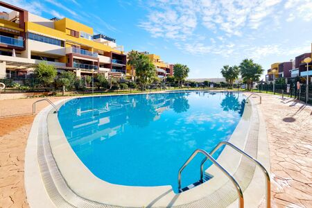 Torrevieja, Spain - November 4, 2019: Exterior of modern style new apartments with swimming pool cozy area. Concept of new property, loan mortgage, luxury lifestyle, flats for rent holidays. Spain