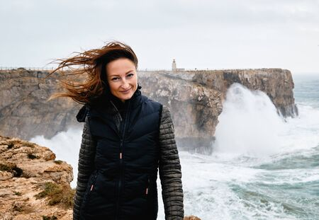 Millennial Caucasian woman her hair fluttering in the wind posing looking at camera standing on the edge of cliff, stormy Atlantic Ocean on background. Fortaleza Sagres Fort. Algarve. Portugal