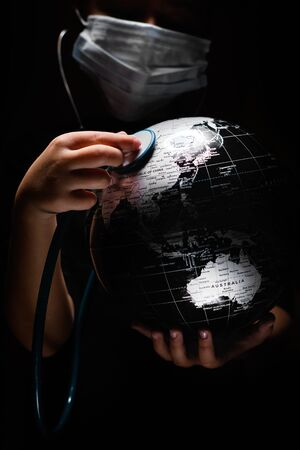 Kid hold globe put stethoscope on sphere, face covered in mask on black background. Ecological problems disasters. COVID-19 pandemic infection disease concept image