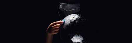 Kid hold globe put stethoscope on sphere, face covered in mask on black horizontal background. Ecological problems disasters. COVID-19 pandemic infection disease concept image, copy space for text