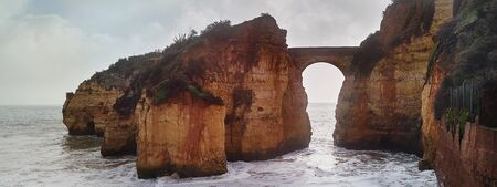 Panoramic image, surrounded by cliffs Praia dos Estudantes or Beach of Students in Lagos, Algarve. Beautiful arch link one of the rocks with the mainland landscape during cloudy weather. Portugal