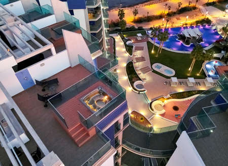 Orihuela, Spain - January 27, 2019: Top view modern luxury architectural residential complex with swimming pools near Mediterranean Sea evening view located in Punta Prima, Torrevieja. Spain. España