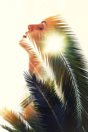Double exposure art photo side view face of woman combined with green lush palm tree leaves over white background. Beauty and fashion, ecological environment, travel and summer holidays concept
