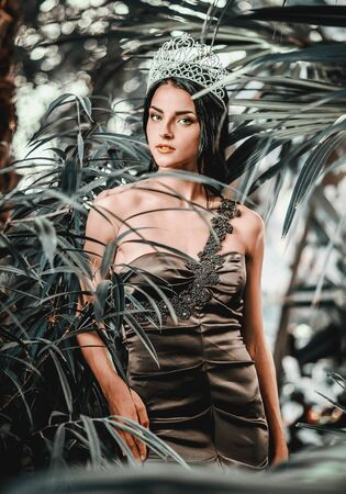 Gorgeous young 20s woman wearing long evening elegant dress and tiara on head posing surrounded by lush tropical foliage trees. Beauty, make up and fashionable store clothes ad for life event concept
