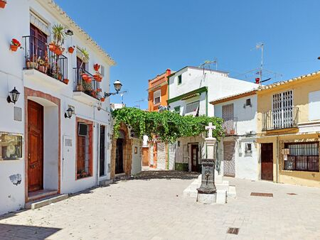 Pretty charming houses decorated with flowerpots ivy leaves in empty small square of Denia old town, spanish historical coastal city in province of Alicante Costa Blanca. Espana. Spain