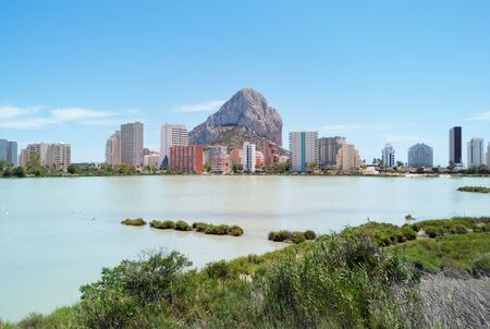 Across salt lake distant view to Parque natural Penon de Ifach or Penyal de Ifac and high rise coastal buildings in Calp Calpe spanish touristic popular city. Province of Alicante, Costa Blanca, Spain