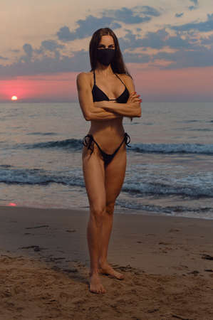 Sensual pretty girl wear black color cloth mask and bikini pose on nature at sunrise near sea. Concept covid-19 outbreak. Obligatory compulsory use face masks outdoors. Fashion and beauty full length Stock fotó