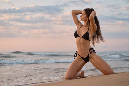 Sexy millennial single woman pose on beach near sea. Beauty and fashion, travel and vacation summer holidays, sexy slim girls with perfect body and summertime collection, fitness bikini model concept 写真素材