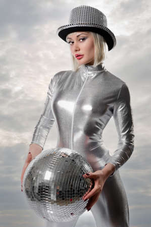 Beautiful young woman with a disco ball pose on cloudy sky background. Concept of party, nightlife