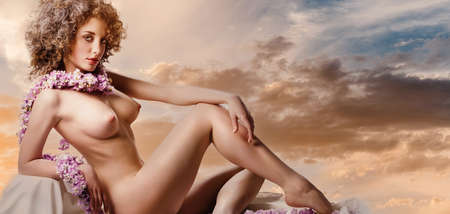Beautiful naked young woman sit on couch pose over cloudy sunset sky background