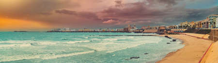 Panoramic wide angle view of Cadiz townscape during sunset, picturesque landscape Atlantic Ocean surf, moody sky, bright cloudy sky over the water. Southwestern Spain. Vacation, landmarks concept
