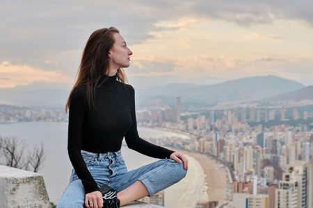 Brown haired tourist woman sit on edge enjoy scenic view of Benidorm touristic city with sea, mountain range, evening sky view. Travel destination, tourism, famous places concept. Costa Blanca. Spain