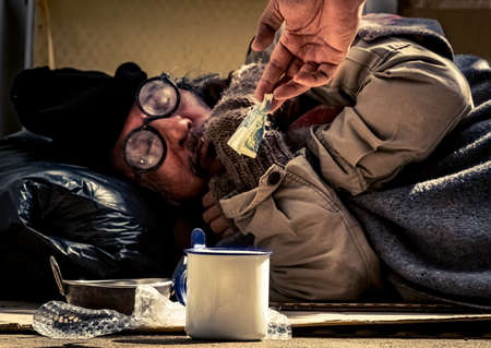 Jobless and homeless man asks for helps and share from passers-by as he suffers from coronavirus pandemic. Stock Photo