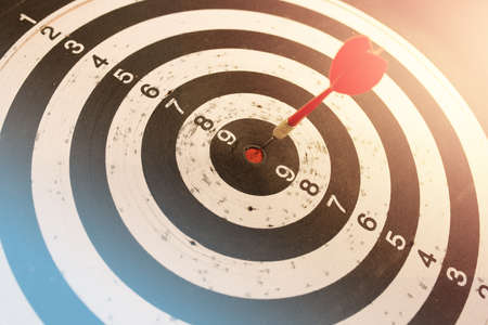 Dart in bulls eye of dartboard with shallow depth of field concept for hitting target Stock Photo