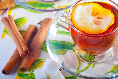 Cup of tea with lemon on transparent saucer near cinnamon sticks photo