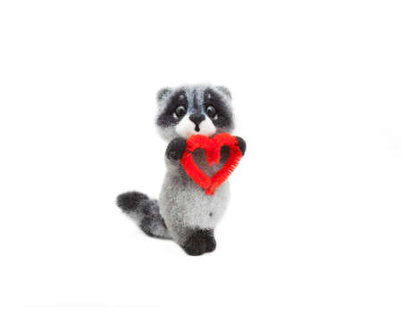 Felted raccoon with the heart in paws