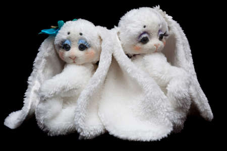 A couple of lovers sewn rabbits isolated on a black background