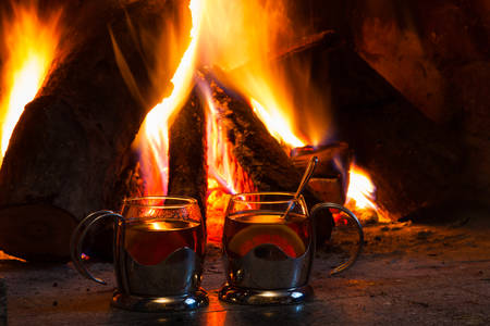 Two cups of tea near the fireplace with flaming woods Imagens
