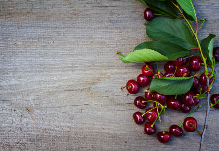 Branch of ripe cherries on the old wooden board Imagens
