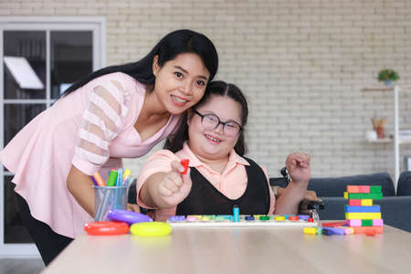 young girl with autism is practicing fun playing with toys at home with his mother. Autistic young students and teachers smiling and looking camera.