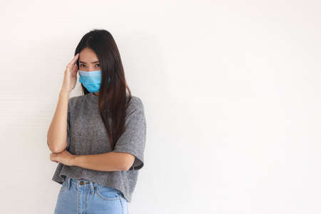 A young Asian woman with long hair wearing a mask has been stressed and anxious from problems caused by the coronavirus covid-19 outbreak. Foto de archivo