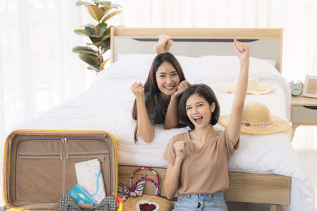 Two young asian women are using laptop to plan travel, book tickets, and booking accommodation online in bedroom. concept of travel in summer and holiday.