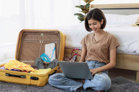 A short haired Asian woman is using her laptop to plan travel, book tickets, and booking accommodation online in his bedroom. concept of travel in summer and holiday.