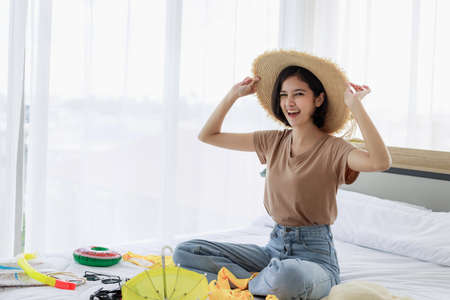 Young Asian woman smiling and experimenting with hats and packing suitcases for summer vacation travel in his bedroom. concept of travel in summer and holiday.
