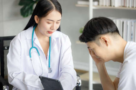 Beautiful young Asian female doctor is recording a medical history on the clipboard and explaining something to the male patient. Medical and health care concepts