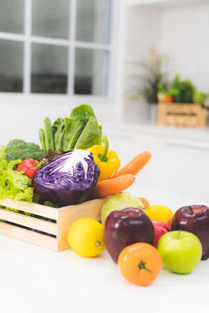 Mixing many fresh fruits and vegetables in a wooden basket placed on a white table in the kitchen.