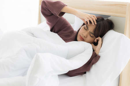 Asian woman sleeps and uses both hands to hold her head because she has stress or headaches from life problems or illness. Stockfoto