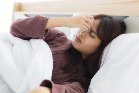 Asian woman sleeps and squeezes her eyebrows because she has stress or headaches due to life problems or illness.