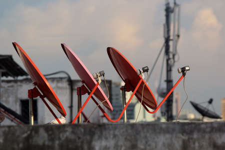 Three a Satellite dish on the roof in the evening  Stock Photo - 21610146