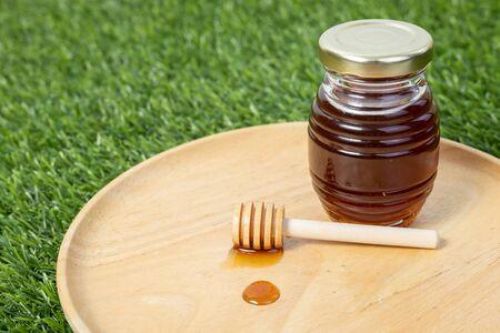 Fresh honey in glass jars on wooden cutting board. honey dipper in wooden bowl.