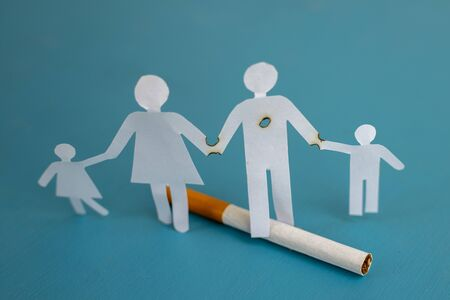 Paper cut of family destroyed by cigarettes. Drugs destroying family concept. Quit smoking for life on World no Tobacco day concept. World no tobacco day. Copy space for advertisers. Zdjęcie Seryjne
