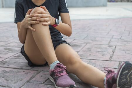 The young sport woman holding knee in pain suffering muscle injury after running.