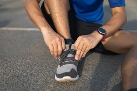 Running shoes. closeup of man tying shoe laces. Sport fitness runner getting ready for jogging in the running track. 免版税图像