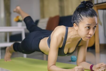International Day of Yoga concept Asian woman doing meditation for yoga athlete plank on an exercise mat at home.